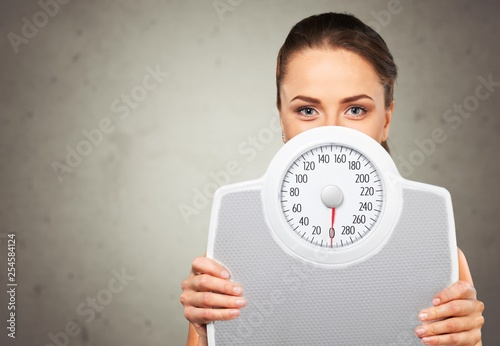 Leinwanddruck Bild Beautiful young s woman holding scales