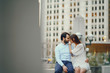 beautiful long-haired girl in summer dress with her handsome husband in white shirt and pants sitting in sunny Chicago