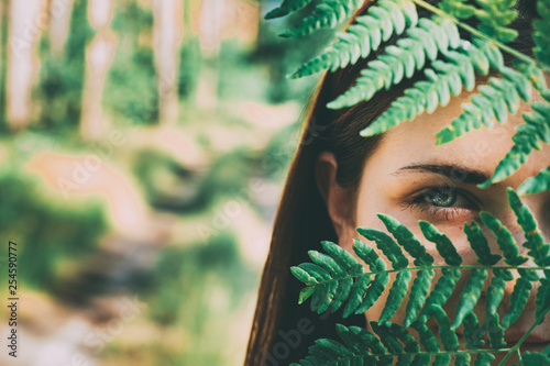 Leinwanddruck Bild Portrait Of A Young Happy Beauty Red Hair Girl Woman Holding Fern Leaf Up To Face In Summer Park Forest