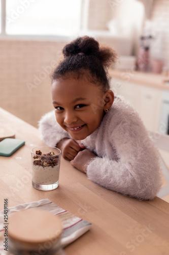Dark-eyed girl feeling cheerful while having dessert at home