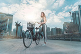 Beautiful Caucasian woman with long brown hair wearing a gray sports outfit about to ride her bike on a bright sunny day
