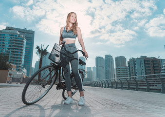 Beautiful Caucasian young woman with long brown hair wearing a gray sports outfit about to start riding her bicycle with a basket with a city background on a bright sunny day