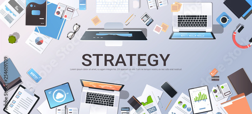 business strategy marketing plan concept top angle view desktop laptop smartphone tablet screen paper documents financial analysis report office stuff horizontal
