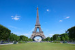 Eiffel Tower in Paris and empty green field of Mars meadow in a sunny summer day, clear blue sky