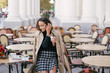 Leinwanddruck Bild - Young beautiful woman drinking coffee in a street cafe