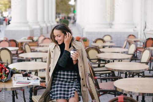 Leinwanddruck Bild Young beautiful woman drinking coffee in a street cafe