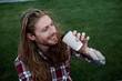 Cheerful long haired man drinking coffee on the grass