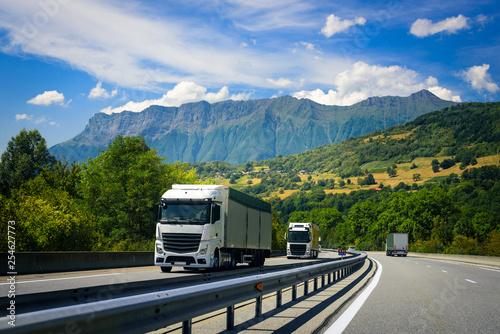 obraz lub plakat Trucks drive on the European highway on the Alpine mountains.