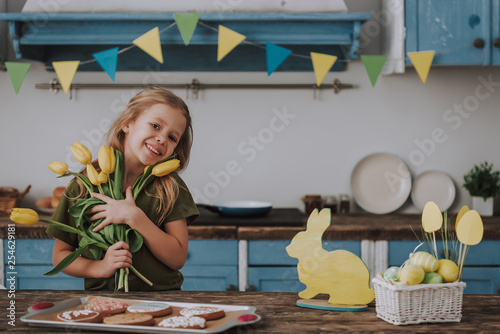 Charming girl holding yellow tulips on kitchen