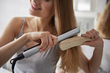 Pretty young lady using flat iron for hairstyle