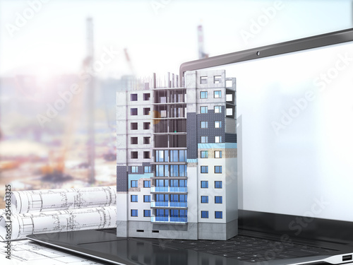 Concept of building a residential building. The layout of the residential building with the facade insulation scheme is located on the laptop. 3d illustration - 254633325