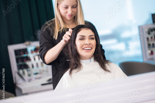 Beautiful brunette woman getting haircut from female blonde hairdresser at beauty salon