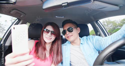 Leinwanddruck Bild couple take selfie in car