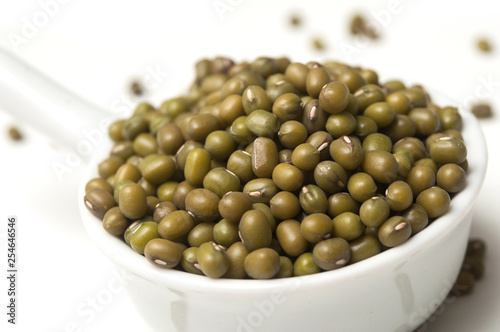 Closeup of mungo beans in a white spoon  on white background - 254646546