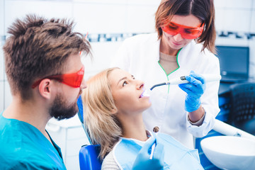 Dentists in red glasses lighting dental seal with ultraviolet lamp