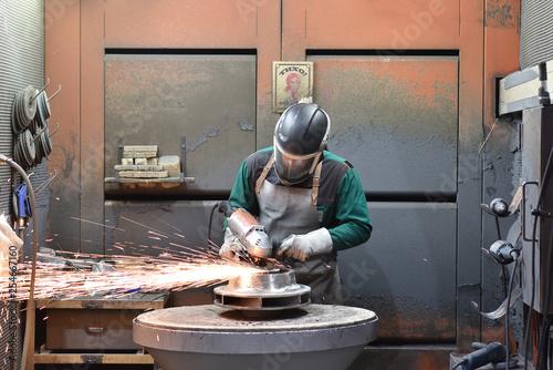 Foto Murales Arbeiter in der Industrie bearbeitet Werkstück aus Stahl mit einer Schleifmaschine // Worker in the industry processes steel workpiece with a grinding machine