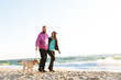 Attractive young couple walking at the beach