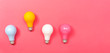 Colored light bulbs on a pink paper background