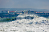 Strong and dangerous storm in the Black sea. Beautiful and big storm wave in Gelendzhik Bay on the background of the resort of Gelendzhik, waterfront and lighthouse. In the background, hotels