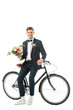 cheerful groom standing near bike and holding wedding bouquet while looking at camera isolated on white