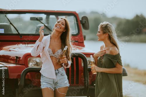 Leinwanddruck Bild Attractive young women standing by a convertible car