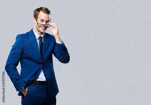 Leinwanddruck Bild young businessman in glasses, against grey