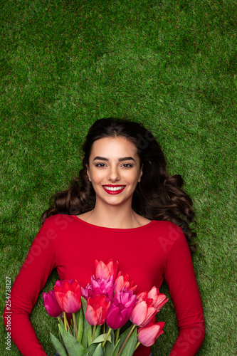 Happy woman with tulips lying on meadow  - 254738127