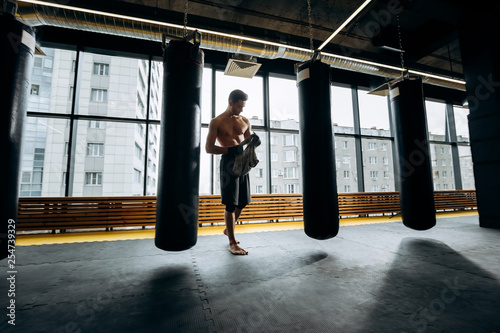 Guy with a naked torso dressed in the black shorts stands next to the punching bags against the background of panoramic windows in the gym