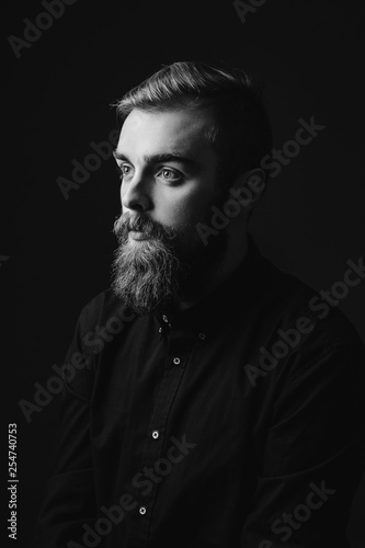 Black and white portrait of a stylish man with a beard and stylish hairdo dressed in the black shirt on the black background