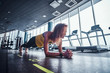Fitness woman doing the plank in the modern gym. Fashion, sport, motivation