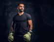 Leinwanddruck Bild - Portrait of a brutal professional fighter in a black shirt and gloves looking sideways. Studio photo against a dark textured wall