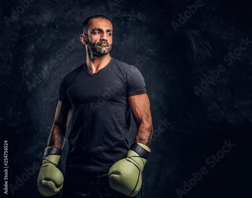 Leinwanddruck Bild Portrait of a brutal professional fighter in a black shirt and gloves looking sideways. Studio photo against a dark textured wall