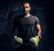 Leinwanddruck Bild - Portrait of a brutal professional fighter in a black shirt and gloves looking at a camera. Studio photo against a dark textured wall