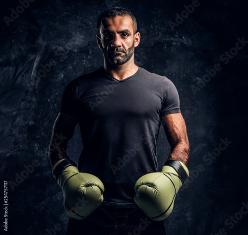 Leinwanddruck Bild Portrait of a brutal professional fighter in a black shirt and gloves looking at a camera. Studio photo against a dark textured wall