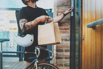 Courier bike delivery food service at home. Man courier delivered the order no name bag with food.