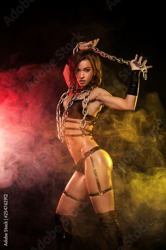Sensual provocation of a sexy woman with chains on black background. BDSM concept - 254762912