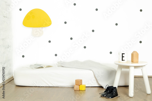 Simple kid's bedroom interior with a white mattress on the floor and yellow mushroom lamp on the wall