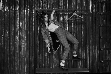 Black-white portrait of a sexy girl in grunge style. Dramatic black and white photo of a beautiful woman on a dark background. Female model in Denim jacket, plaid pants, white socks and leopard shoes