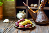 Olives in a bronze platel on a wooden kitchen table