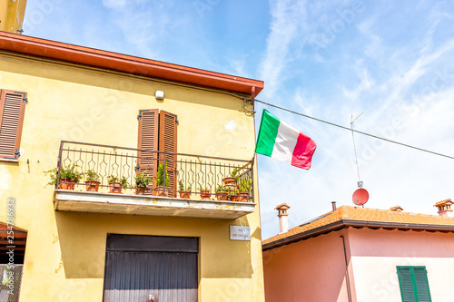 Chiusi, Italy street with Italian flag on building exterior hanging on balcony of apartment in small historic medieval town village in Umbria during day with orange yellow bright vibrant wall and sign