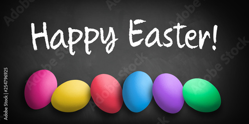 Leinwanddruck Bild colored eggs with letters forming the word easter on a blackboard