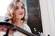 Pretty young gilrl musician in white dress with double bass.