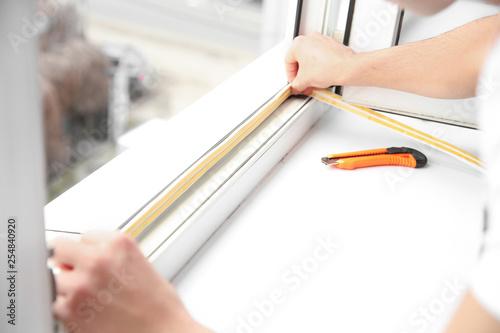 Leinwanddruck Bild Young worker installing window in flat