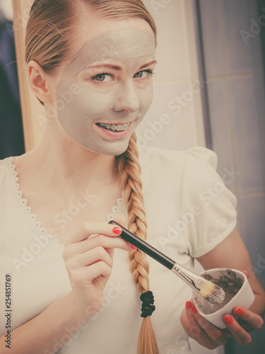 Leinwanddruck Bild Happy young woman applying mud mask on face