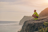 Sportsman making pause after workout on a tropical cliff.