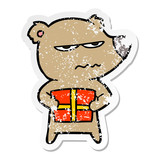 distressed sticker of a angry bear cartoon holding present