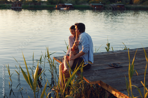 Leinwanddruck Bild Young loving couple enjoys by the river during the sunset