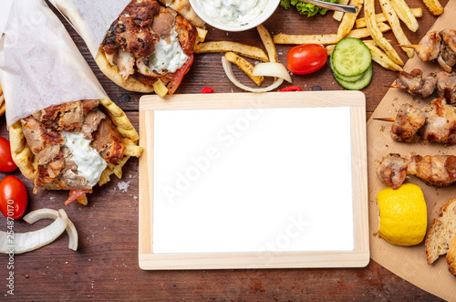 Gyro pita, shawarma. Two pita bread wraps with meat, and blank board on wooden table, copy space - 254870170