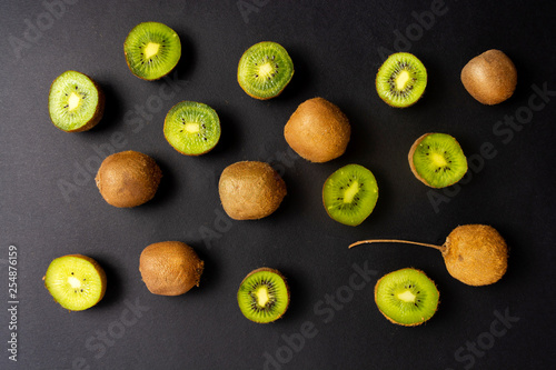 Kiwi on black background top view - 254876159