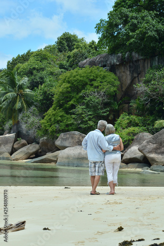 Leinwanddruck Bild Portrait of elderly couple hugging on tropical beach
